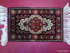 Kis perzsa szőnyeg eladó. Méret: 53x32 cm.